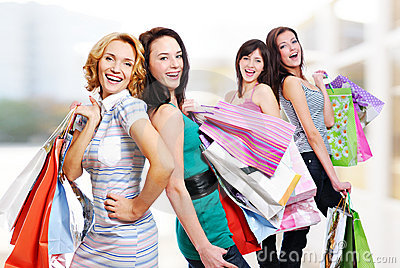 Four cheerful adult girls with  purchases