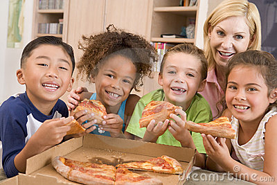 Four children indoors with woman eating pizza
