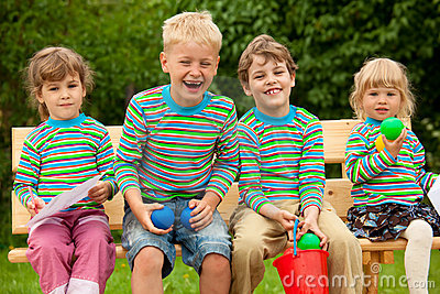 Four children in laugh sitting on bench