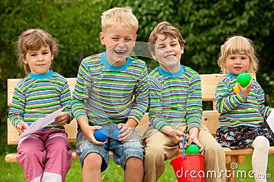 Four children in laugh sitting on bench