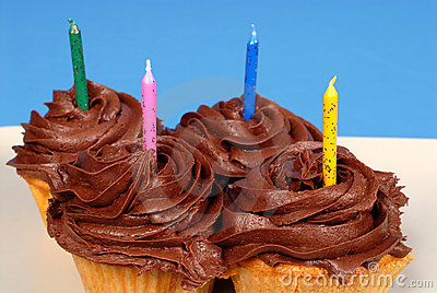 Four chocolate frosted cupcakes with candles
