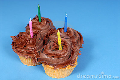 Four chocolate frosted cupcakes with candles with a blue backgro