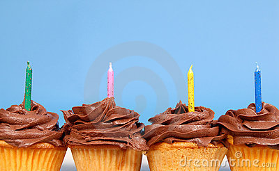 Four chocolate frosted cupcakes in a row with candles