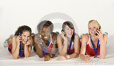 Four Female Athletes Lying Down, talking on Phones