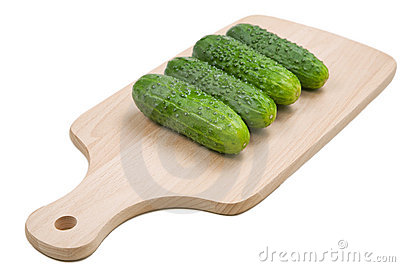 Four fresh green cucumbers on cutting board