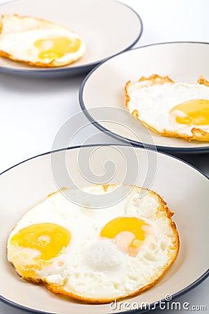 Four fried eggs on three plates