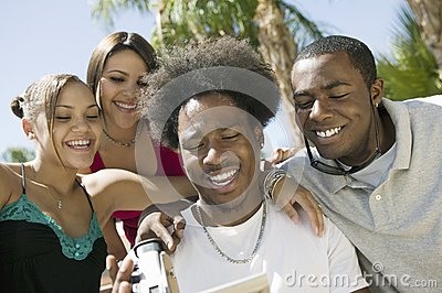 Four friends in back yard looking at video camera screen front view