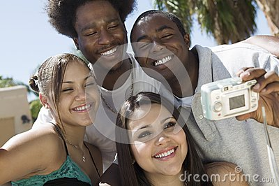 Four friends in back yard photographing selves