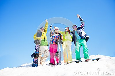 Four friends with snowboards standing in snow