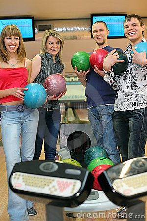 Four friends stand near tenpin bowling with balls