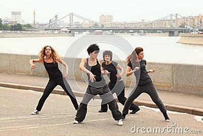Four girls dancing on embankment