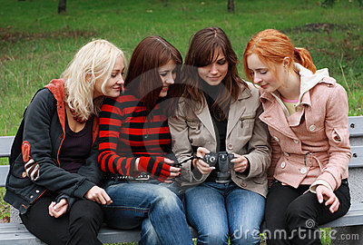 Four girls having fun with a digital camera