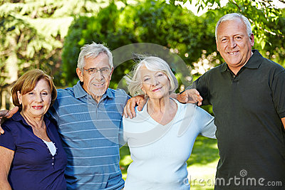 Four happy senior people in nature