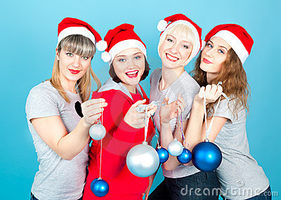 Four happy women with new year balls