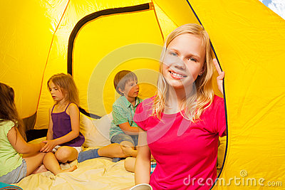 Four kids sit in a tent