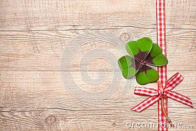 Four leaf clover over wooden background