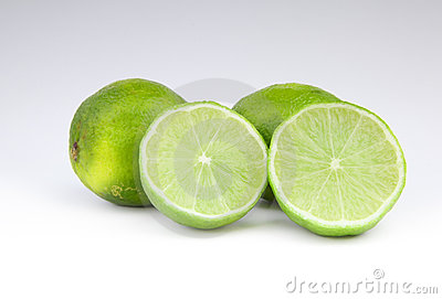 Four lime fruit on gray background
