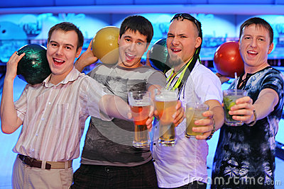 Four men hold balls and glasses of beer