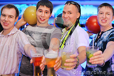 Four men hold balls and glasses in bowling