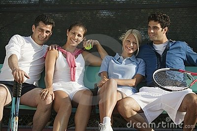 Four mixed doubles tennis players on bench
