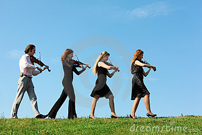 Four musicians go and playing violins against sky