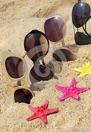 Four pairs of sunglasses on the beach