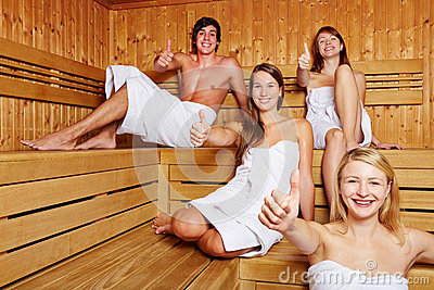 Four people in sauna holding thumbs