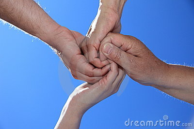 Four persons holding hands