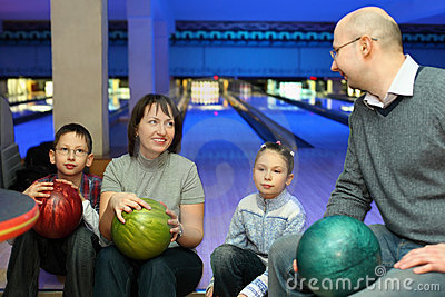 Four persons sit communicate in bowling club