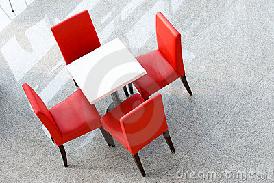 Four red chairs at a table
