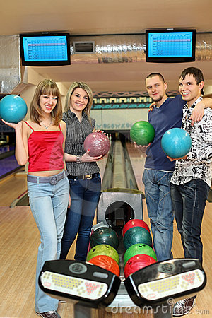 Four students stand near tenpin bowling with balls