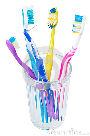 Free Four Tooth Brushes And Interdental Brush In Glass Royalty Free Stock Images - 49344739