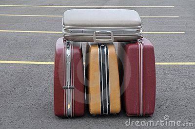 Four vintage suitcases on a parking lot