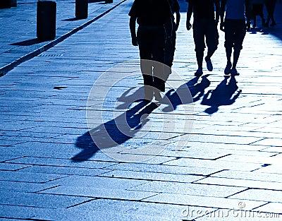 Four walking people shadows