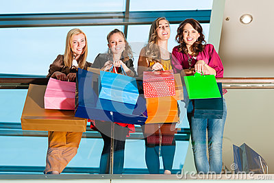 Four women friends shopping in a mall