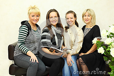 Four women sit on black leather couch