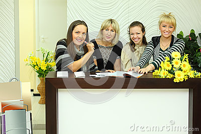 Four women sit in reception area with magazines