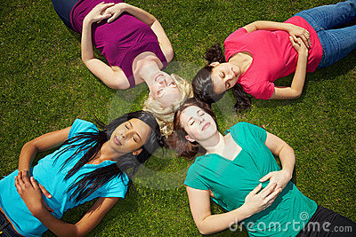 Four women sunbathing in a park