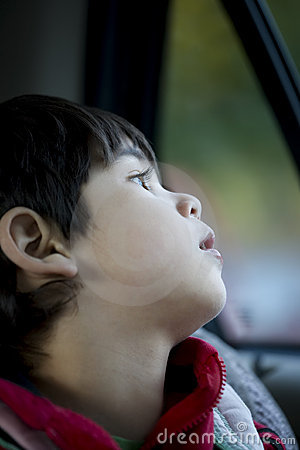 Four year old boy looking quietly out window