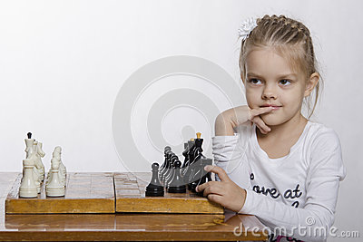 Four-year-old girl with a sly look, plays chess