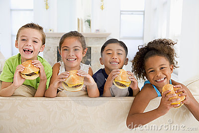 Four young children eating cheeseburgers