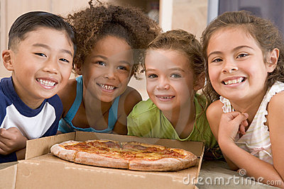 Four young children indoors with pizza smiling