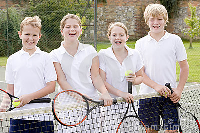 Four young friends on tennis court smiling