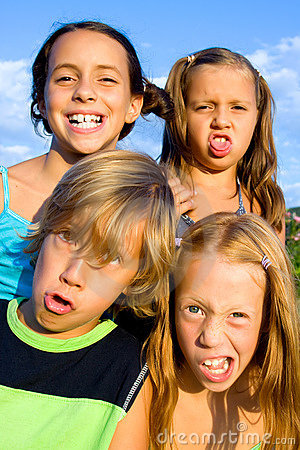 Four young kids making funny faces