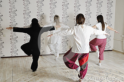 Four young women practice yoga
