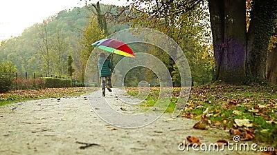 Fröhlicher kleiner Junge springt mit geschecktem Regenschirm im Herbstpark stock video