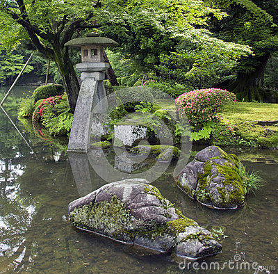 Fragment of japanese garden with stone lantern and big rocks covered with moss