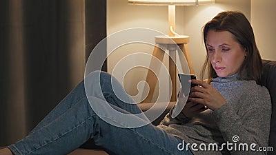 Frau auf der Couch in einem gemütlichen Zimmer und am Abend mit Smartphone zum Internet surfen Entspannung und stock video
