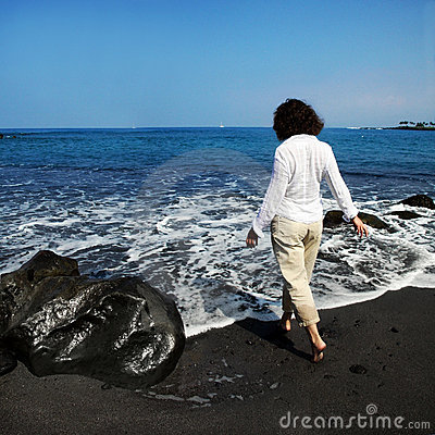 Frau auf schwarzem Sandstrand