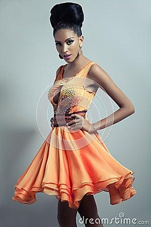 Frau in der Orange erweiterte sich Kleid